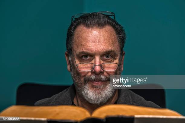 gray bearded man with reading eyeglasses reading vintage book - cmannphoto stock pictures, royalty-free photos & images