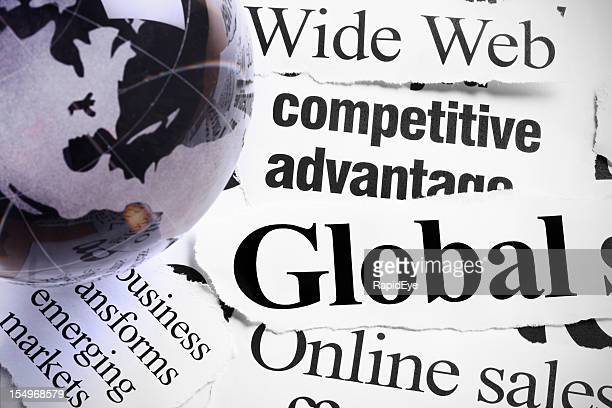 Gray glass globe paperweight on headlines about international Internet business
