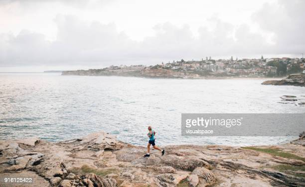 gray hair senior runner running near the ocean - wide stock pictures, royalty-free photos & images