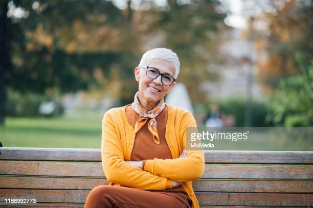 外で楽しむ白髪の女性 - オレンジ色のシャツ ストックフォトと画像