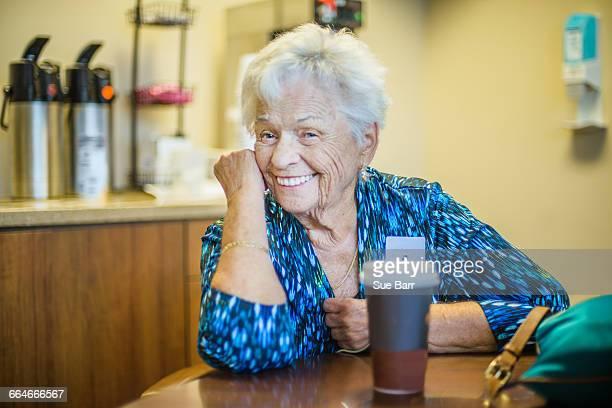 Gray haired woman at table looking at camera smiling
