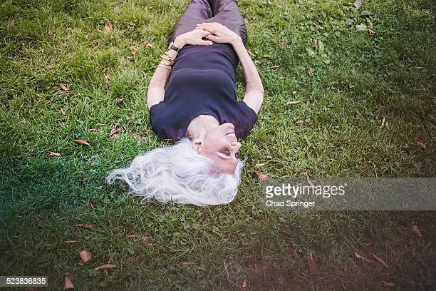 Gray haired woman taking break and enjoying grass in city park