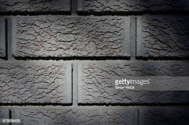gray painted brick wall on the exterior of a building - wall building feature stock photos and pictures