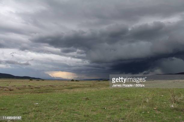 gray storm clouds over green field - james popple stock photos and pictures
