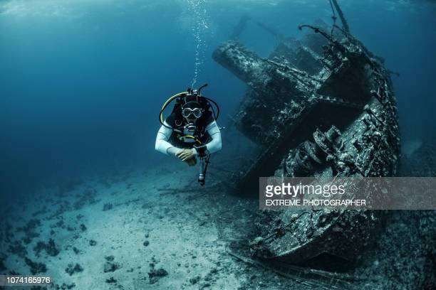gray suited scuba diver diving away from a large underwater shipwreck in the red sea - shipwreck stock pictures, royalty-free photos & images