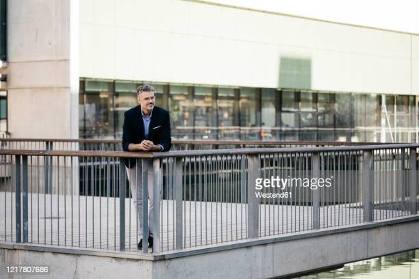 gray-haired businessman having a break in the city - vedação de corrimão imagens e fotografias de stock