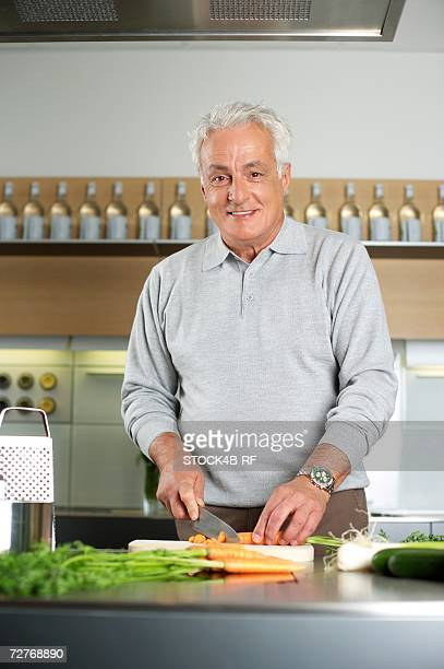 Gray-haired man is cutting vegetables in a kitchen, selective focus