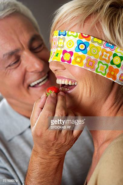 Gray-haired man letting a woman, who's eyes are covered, taste a strawberry, close-up