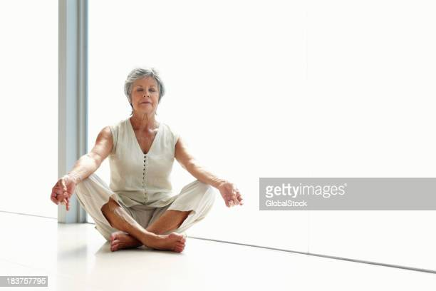 Gray-haired, meditative woman in white clothes, cross-legged