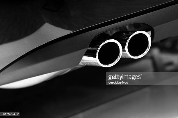 Grayscale photo of car exhaust pipes