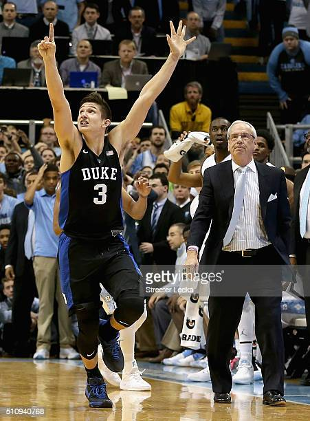 Grayson Allen of the Duke Blue Devils celebrates after defeating the North Carolina Tar Heels 7473 as head coach Roy Williams watches on during their...