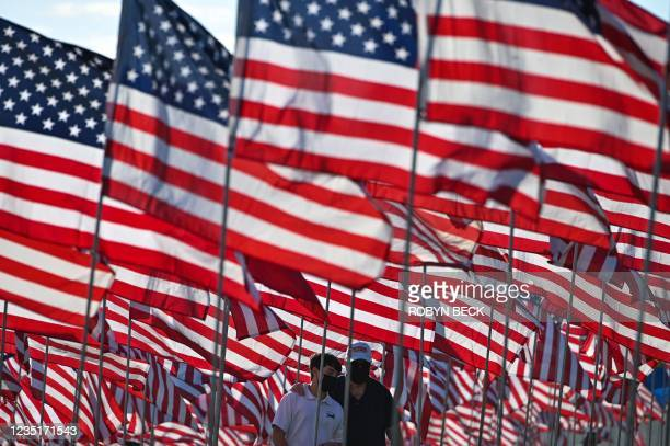 Grayson Kilroy walks with his grandfather Ken Kilroy among American flags displayed to commemorate lives lost in the 9/11 terror attack, on September...