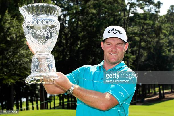 Grayson Murray of the United States celebrates with the trophy after winning on the 18th green during the final round of the Barbasol Championship at...