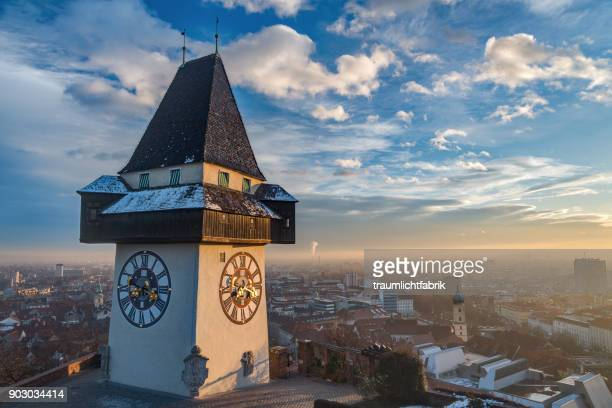 graz clock tower in golden afternoon light - graz stock photos and pictures