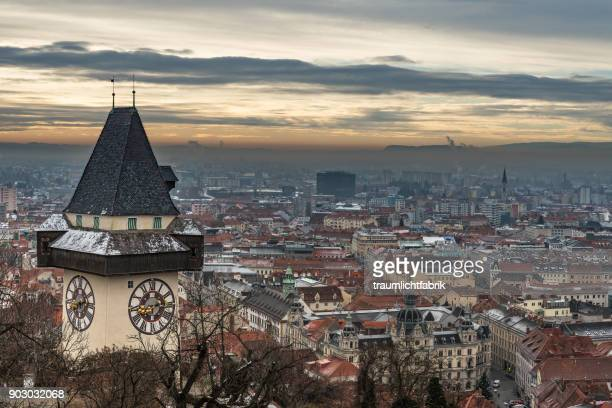 graz clock tower on a december day - graz stock photos and pictures