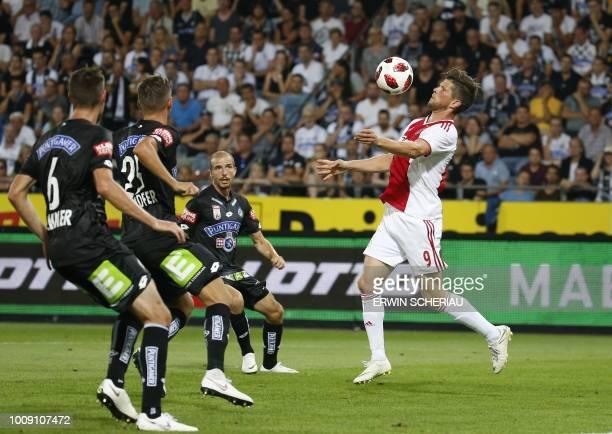 Graz' Markus Lackner, Lukas Spendlhofer and Fabian Koch vie for the ball with Ajax' Klaas-Jan Huntelaar during the UEFA Champions League second...