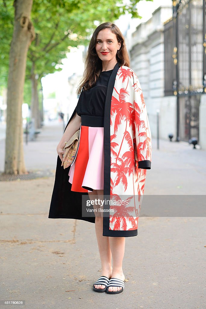 Grazia Germany fashion editor Stephanie Morcinek poses wearing a Fausto Puglisi coat and skirt and Adidas sliders before Atelier Versace show on July 6, 2014 in Paris, France.
