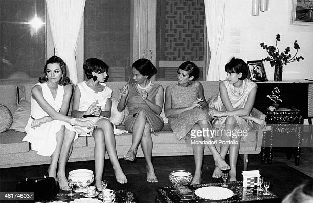 Grazia magazine models sitting on a sofa with the dressmaker of the queen Sirikit Thailand 1965