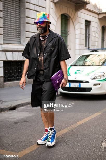 Graziano Di Cintio wearing a black lace top black Prada shirt black shorts with Prada belt colorful sneakers purple Prada bag and tie dye hat is seen...