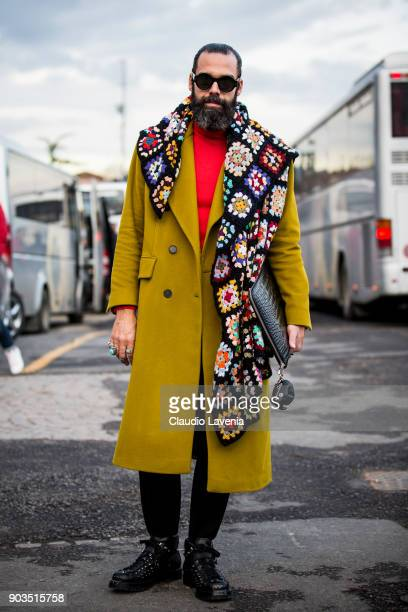 Graziano Di Cintio wearing mustard wool coat clutch and a scarf with flower print is seen during the 93 Pitti Immagine Uomo at Fortezza Da Basso on...
