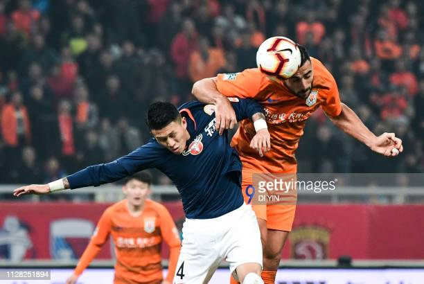 Graziano Pelle of Shandong Luneng compete for a header with Luo Qin of Beijing Renhe during the 2019 Chinese Super League match between Shandong...