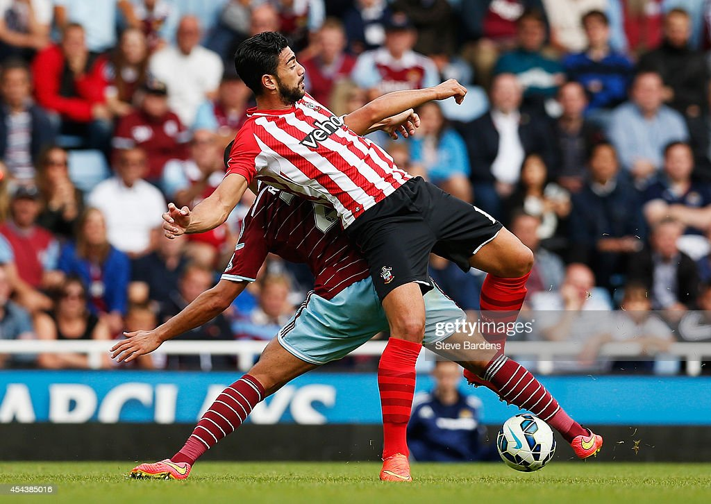 Graziano Pelle of Southampton is challenged by Winston Reid of West Ham United during the Barclays Premier League match between West Ham United and Southampton at Boleyn Ground on August 30, 2014 in London, England.