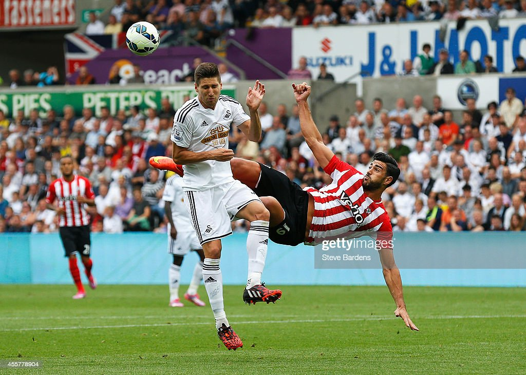 Graziano Pelle of Southampton volleys challenged by Federico Fernandez of Swansea City during the Barclays Premier League match between Swansea City and Southampton at Liberty Stadium on September 20, 2014 in Swansea, Wales.