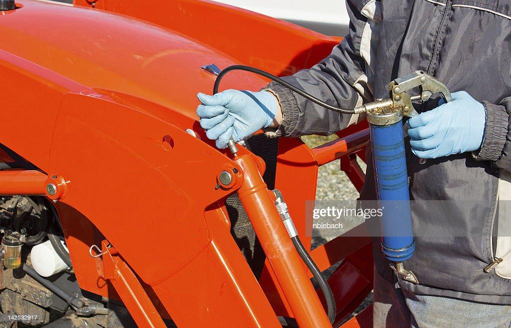 Greasing Tractor Piston : Stock Photo