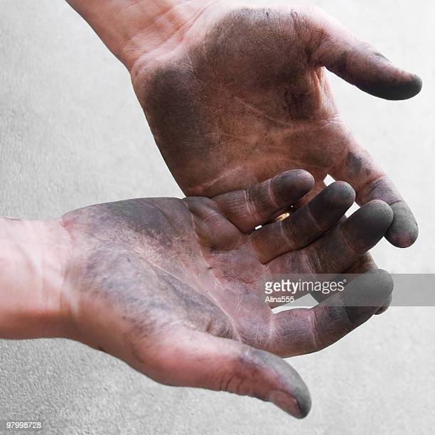 Greasy hands of a mechanic above the asphalt