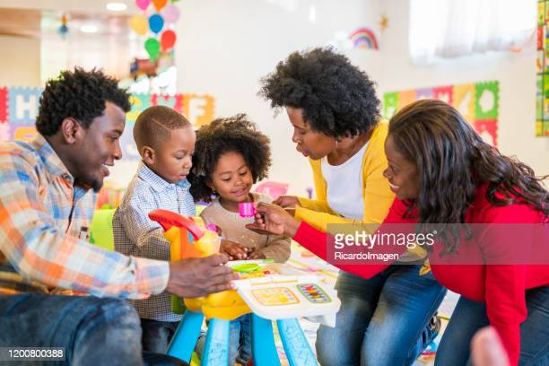 great afro latin family consisting of mom, grandmother, girl and boy of approximately 4 to 5 years old and dad play in a fun way in beautiful colorful recreation room - 8 9 years stock pictures, royalty-free photos & images