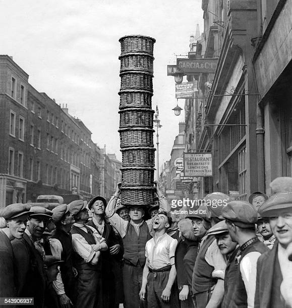 Great Britain England London Basket carrier at Covent Garden Market balancing a pile of baskets on his head Photographer Eduard Schlochauer Published...