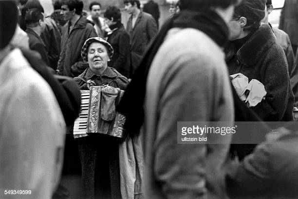Great Britain England London blind female beggar playing accordion on the street in Portobello Road