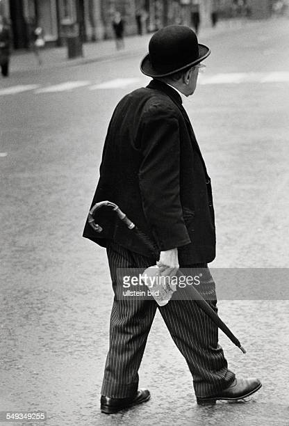Great Britain England London street scene man on the street with traditional bowlerhat and umbrella