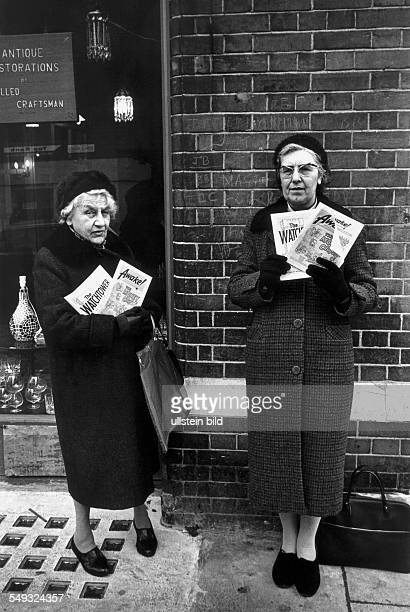 Great Britain England London two elderly women from Jehovah's Witnesses offer their magazin Awake and Watchtower in the street