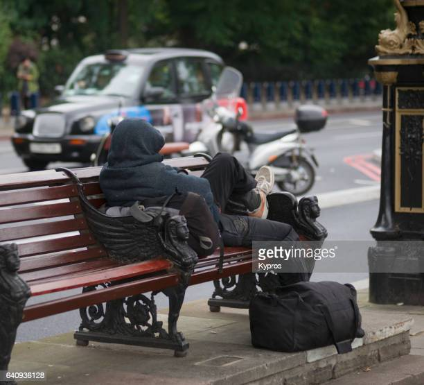 uk, great britain, england, london, view of homeless person resting on wooden bench - homeless person stock pictures, royalty-free photos & images