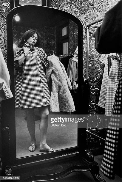 Great Britain England London young woman in fashion boutique 'Bus Stop' in Kensington looking into mirror with new dress
