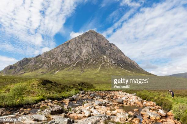 Great Britain, Scotland, Scottish Highlands, Glen Etive, Mountain massif Buachaille Etive Mor, River Coupall, male tourist photographing Mountain Stob Dearg