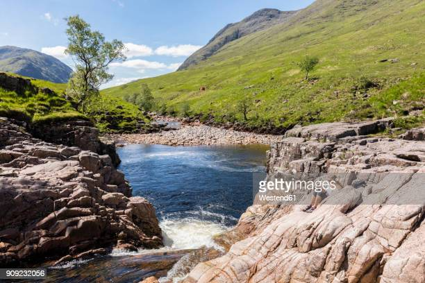 Great Britain, Scotland, Scottish Highlands, Glen Etive with River Etive and Glen Etive Falls, female tourist reading