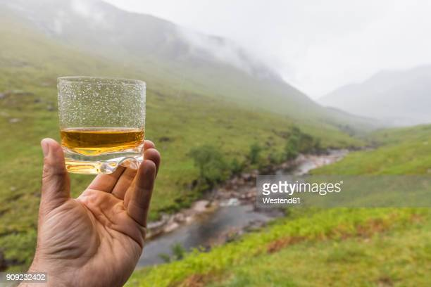 great britain, scotland, scottish highlands, glen etive with river etive and glen etive falls, hand holding scotish whiskey in a glass - falling water stock photos and pictures