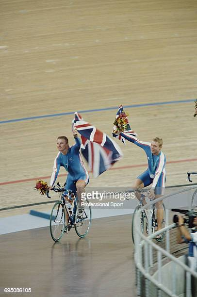 Great Britain team cyclists Craig MacLean and Chris Hoy celebrate with the national flag and bouquets of flowers after finishing in 2nd place to win...