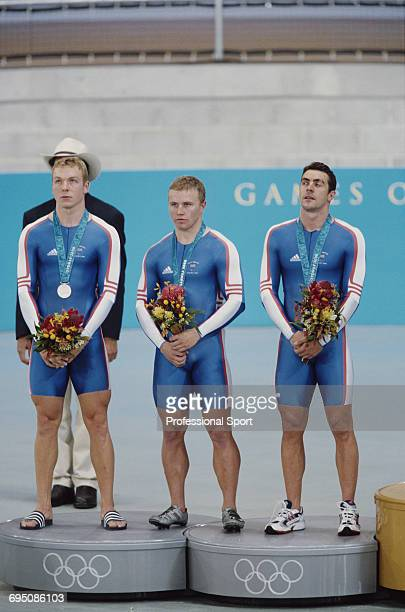 Great Britain team cyclists, from left, Chris Hoy, Craig MacLean and Jason Queally stand together on the medal podium after finishing in 2nd place to...