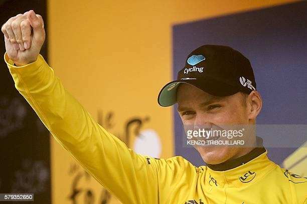 Great Britain's Christopher Froome celebrates his overall leader yellow jersey on the podium at the end of the 1465 km twentieth stage of the 103rd...