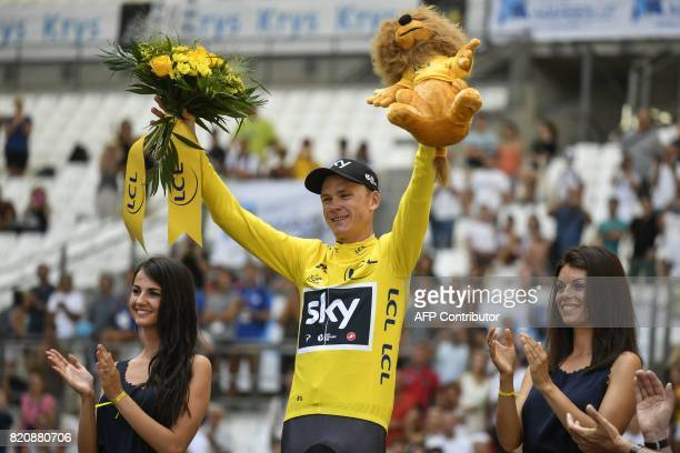Great Britain's Christopher Froome celebrates his overall leader yellow jersey on the podium at the end of a 225 km individual timetrial the...