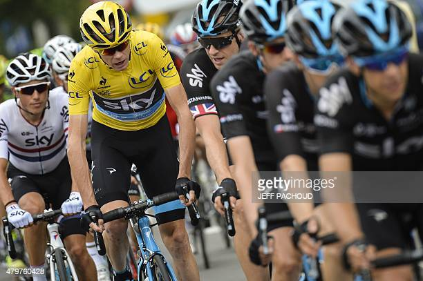 Great Britain's Christopher Froome wearing the overall leader's yellow jersey rides behind his teammates of Great Britain's Sky cycling team during...