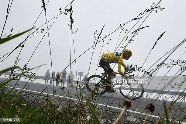 TOPSHOT Great Britain's Christopher Froome wearing the overall leader's yellow jersey rides in the fog during the 197 km tenth stage of the 103rd...