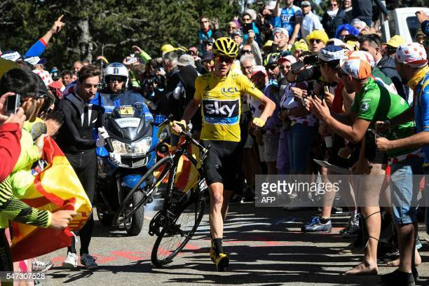 TOPSHOT Great Britain's Christopher Froome wearing the overall leader's yellow jersey carries his bike after falling during the 178 km twelvelth...
