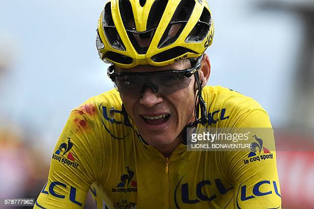 Great Britain's Christopher Froome wearing the overall leader's yellow jersey crosses the finish line at the end of the 146 km nineteenth stage of...