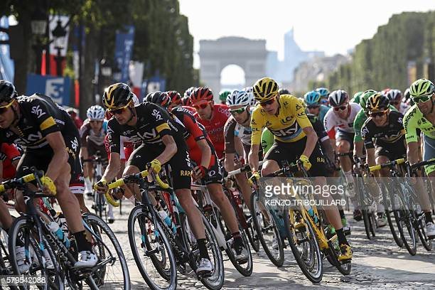 TOPSHOT Great Britain's Christopher Froome wearing the overall leader's yellow jersey rides in the pack on the ChampsElysees avenue decorated with...
