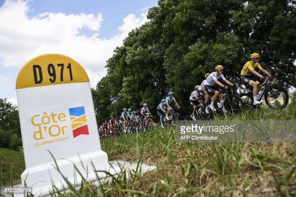 Great Britain's Christopher Froome wearing the overall leader's yellow jersey rides in the pack past a kilometre marker during the 2135 km seventh...