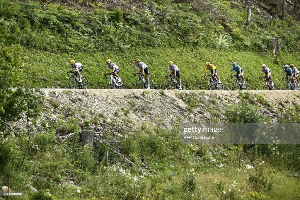 Great Britain's Christopher Froome (5thL), wearing the overall leader's yellow jersey, rides behind his teammates during the 187,5 km eighth stage of the 104th edition of the Tour de France cycling race on July 8, 2017 between Dole and Station des Rousses. /